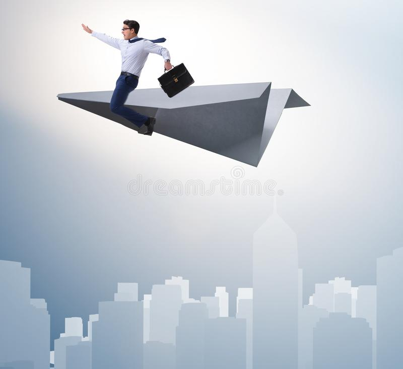 Businessman flying on paper plane in business concept. The businessman flying on paper plane in business concept stock photo