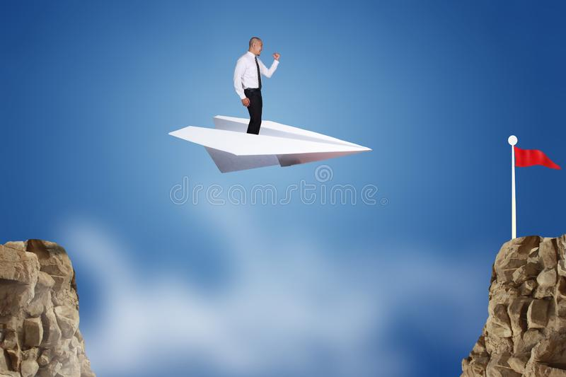 Businessman Flying on Paper Plane. Success vision in business concept. Businessman flying on paper plane across the cliff, conquering adversity with innovation stock photography