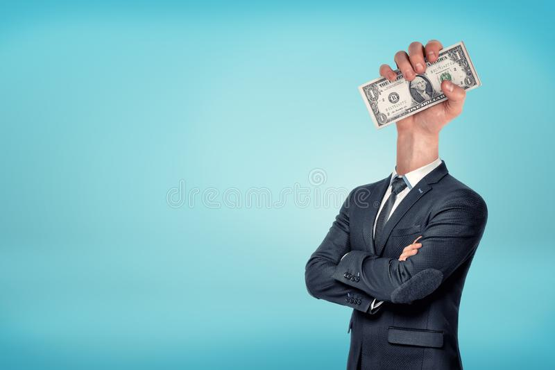 A businessman with folded arms has a large hand holding dollar bills instead of his head. Money addiction. Career and business. Working only for money stock photography