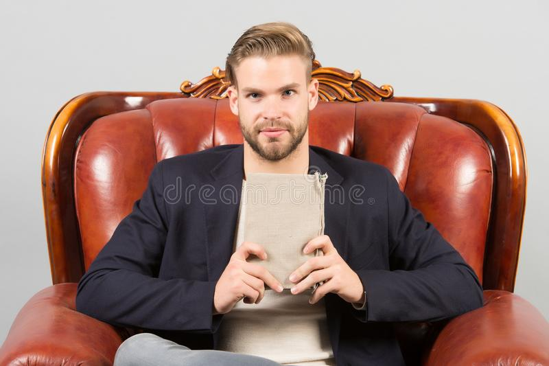 Businessman formal suit sit on leather chair, grey background. Man calm face reading book studying, self developing royalty free stock photography