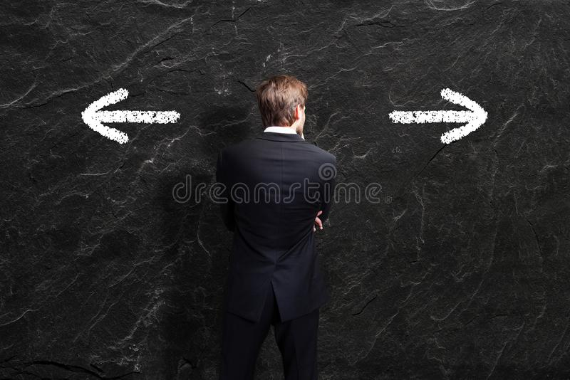 Businessman has to decide between two directions royalty free stock photo