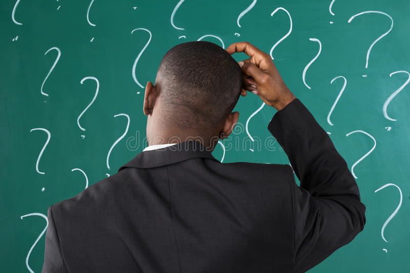 Businessman In Front Of Chalkboard With Question Mark Sign. Rear View Of African Businessman In Front Of Chalkboard With Question Mark Sign stock photography