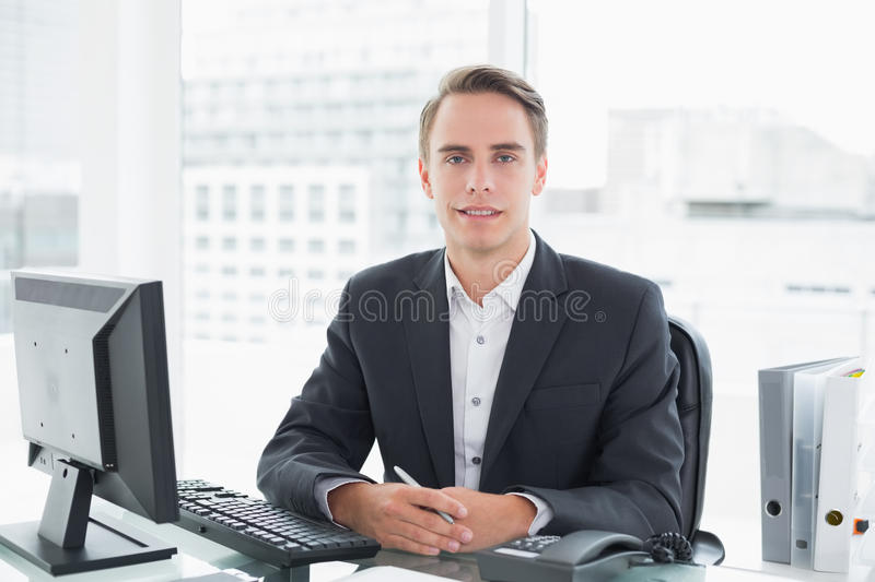 Businessman in front of computer at office desk. Portrait of a smiling young businessman in front of computer at office desk royalty free stock photo