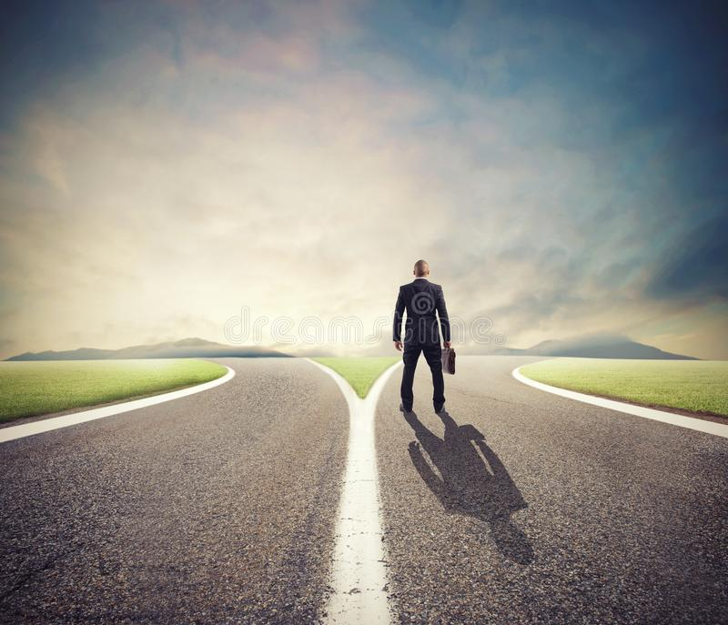 Businessman in front of a crossway must select the right way. Of success royalty free stock image