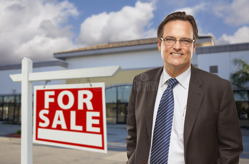 Businessman In Front of Office Building and For Sale Sign. Handsome Businessman In Front of Vacant Office Building and For Sale Real Estate Sign royalty free stock photo