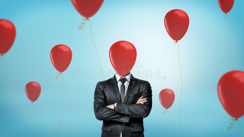 A businessman in front view with crossed arms stands surrounded by many red party balloons with one hiding his face. stock images