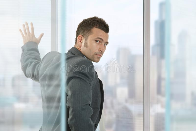 Businessman in front of window looking back. Young caucasian businessman in front of window looking back at business office. Hand on glass, wearing suit, serious stock images