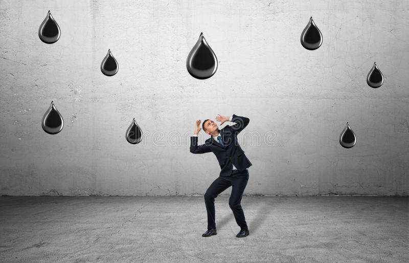 Businessman in full growth protects himself against huge falling oil drops. royalty free stock images