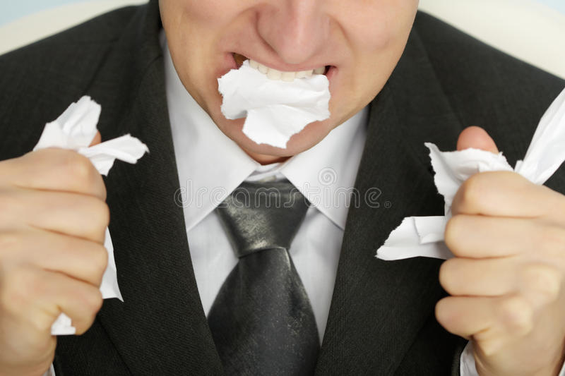 Businessman furiously tearing paper. With his teeth and hands royalty free stock photography