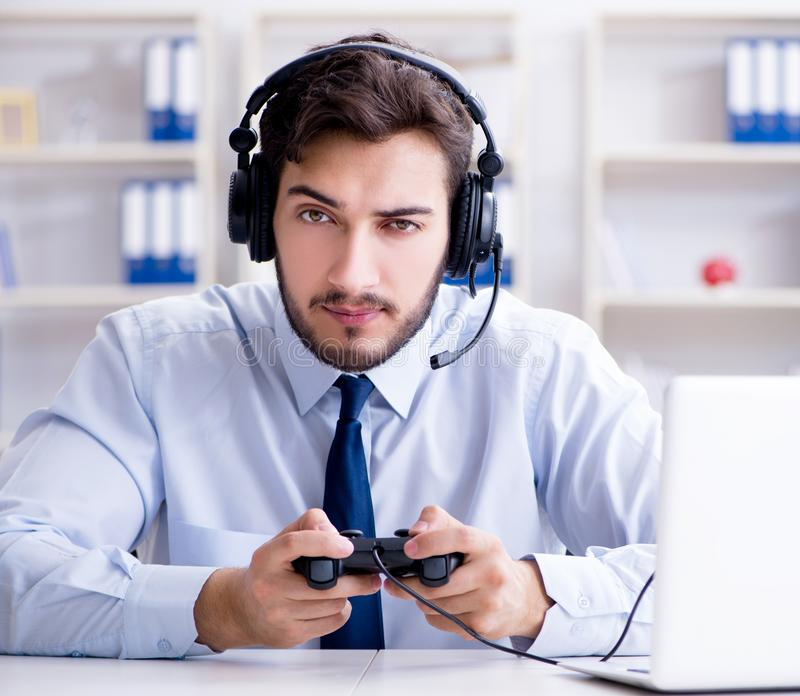 Businessman gamer in office playing games. The businessman gamer in office playing games royalty free stock photo