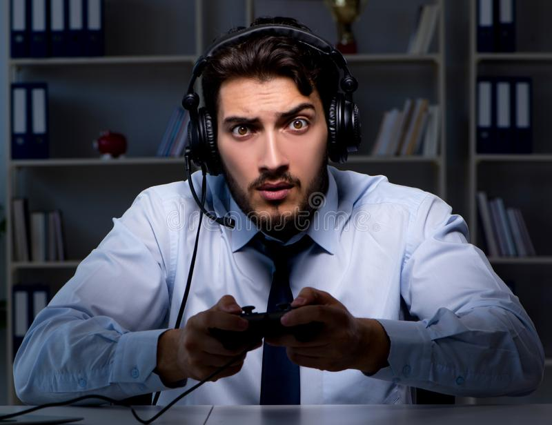 Businessman gamer staying late to play games. The businessman gamer staying late to play games stock image