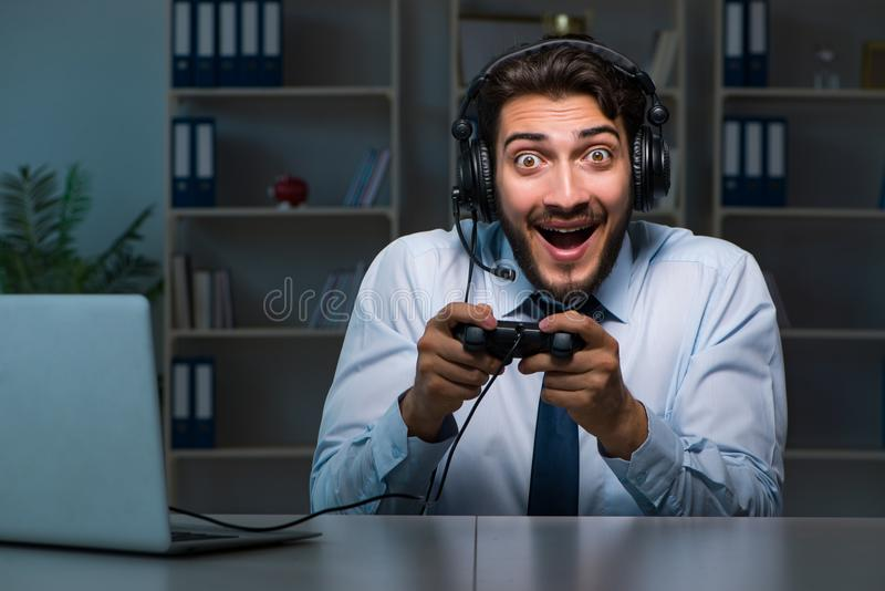 The businessman gamer staying late to play games. Businessman gamer staying late to play games stock images