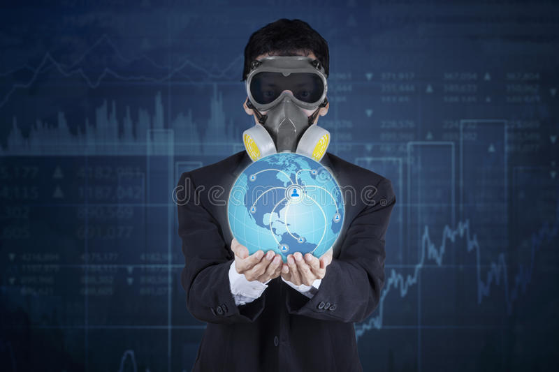 Businessman with gas mask and globe royalty free stock photo