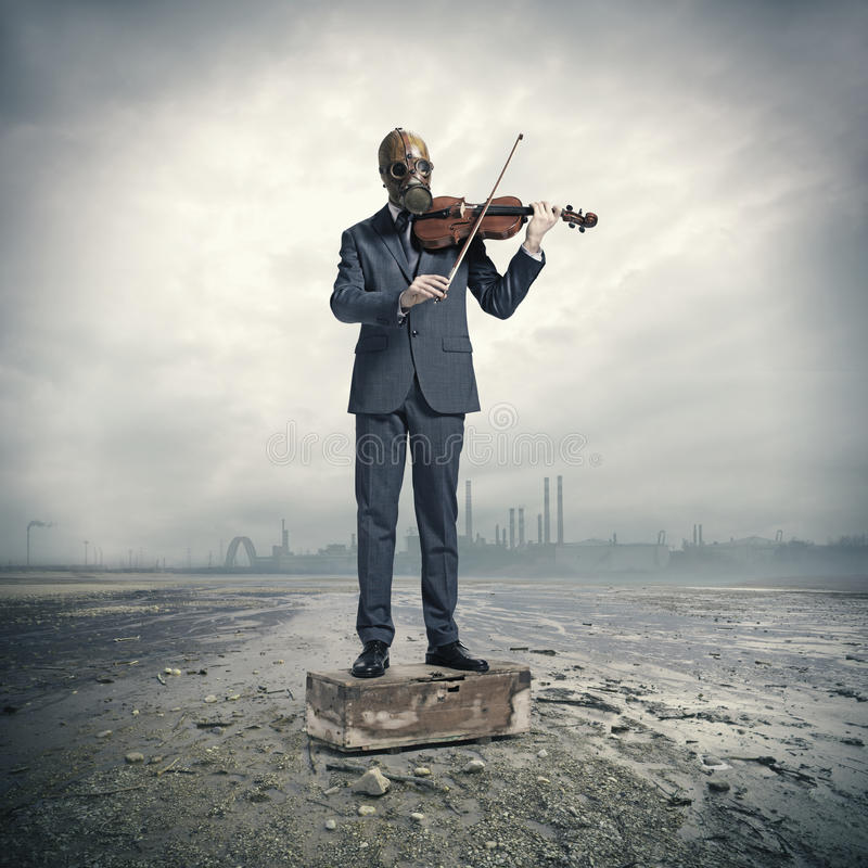 Businessman with gas mask, plays the violin. Environmental disaster: businessman with gas mask, plays the violin royalty free stock photos
