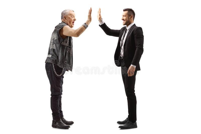 Businessman gesturing high-five with a mature rocker stock photos