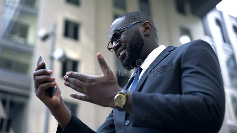 Businessman gets upset after read bad news on smartphone, fired, trouble at work. Stock photo stock photos