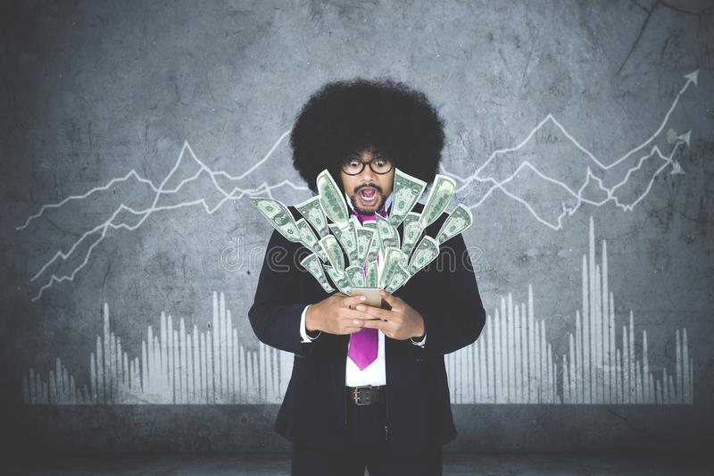 Businessman getting money of his smartphone stock photos
