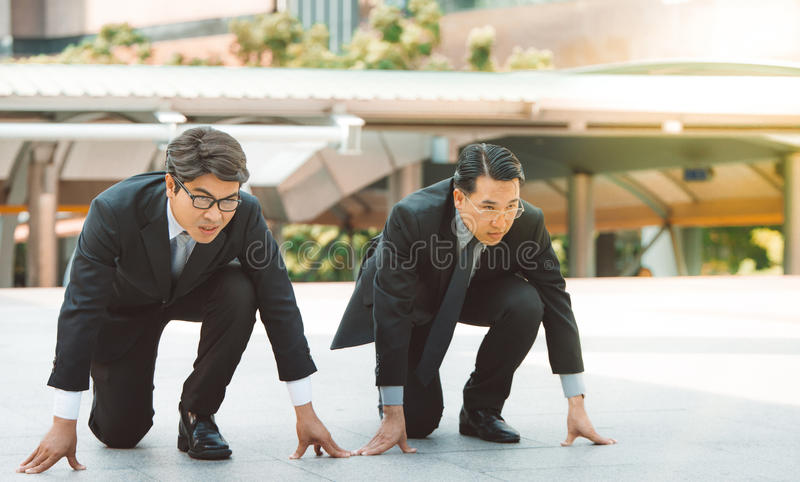 Businessman getting ready for race competition business rival concept. stock photo