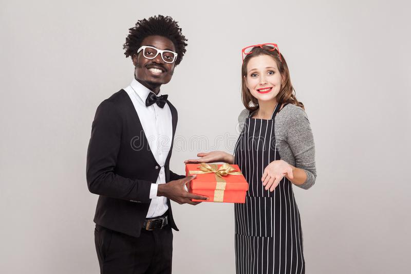 Businessman gives a gift for St. Valentine`s Day her woman. stock photos