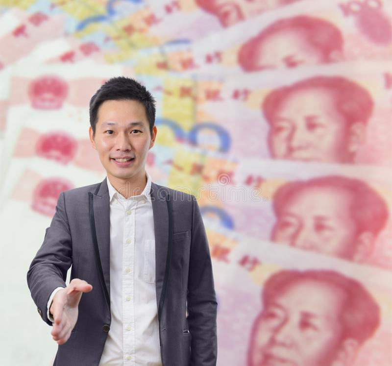 Businessman gives a handshake with China banknote background royalty free stock photo