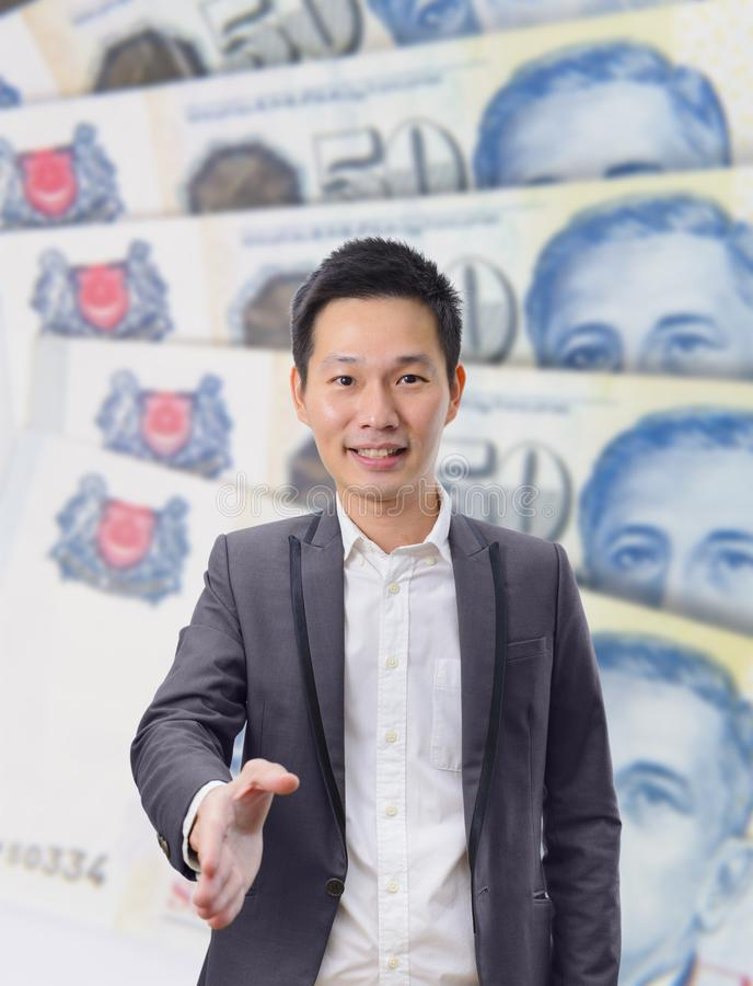 Businessman gives a handshake with Singapore dollar banknote background royalty free stock images