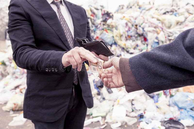 Businessman gives money to a homeless man. In a dump stock image