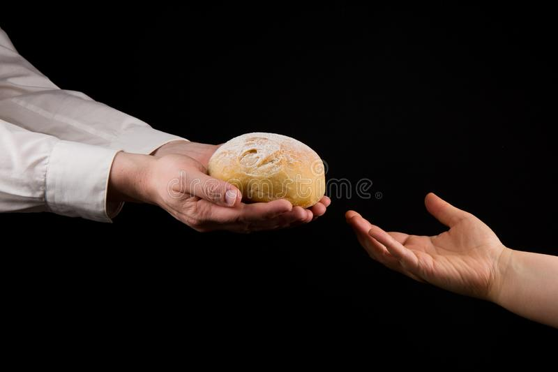 Businessman giving bread to a woman. Helping Hand Concept. stock photo