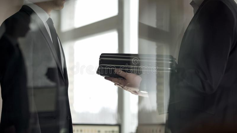 Businessman giving briefcase of money to partner, illegal deal, corruption. Stock photo stock photos