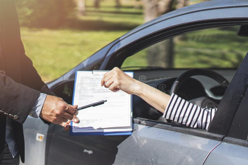 Businessman giving car key, application document with pen stock photos