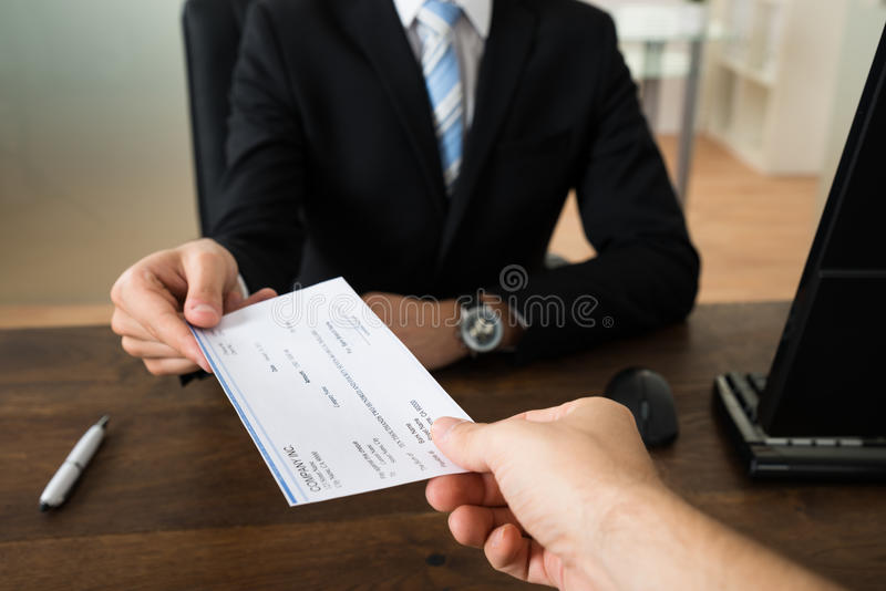 Businessman Giving Cheque To Other Person. Close-up Of Businessman Hands Giving Cheque To Other Person In Office stock photos