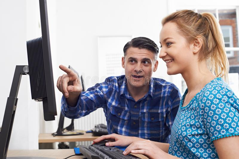 Businessman Giving Computer Training To Female Trainee In Offic. Businessman Gives Computer Training To Female Trainee In Office royalty free stock images