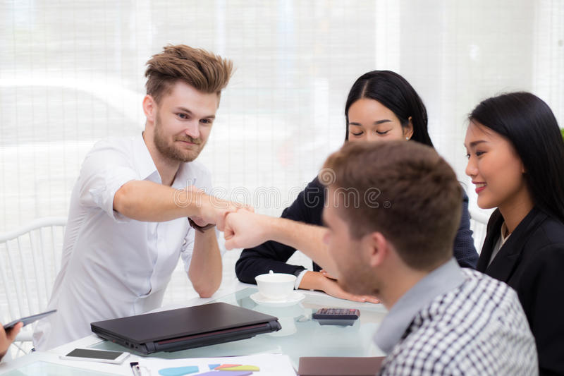 businessman giving fist bump after business achievement in meeting room. stock photo