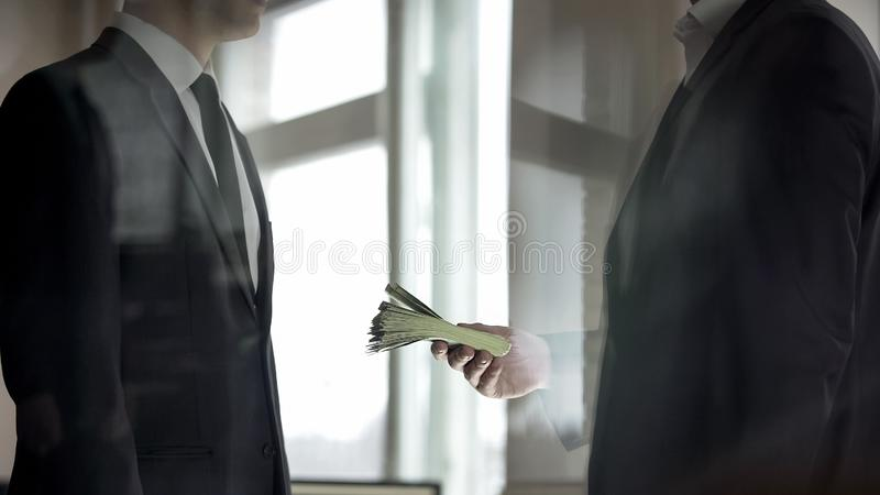 Businessman giving his partner cash, profit from successful business deal. Stock photo stock photos