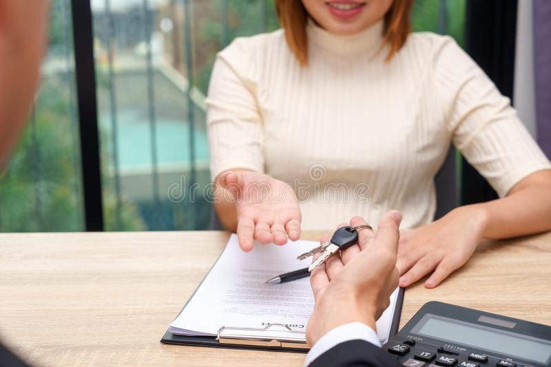 Businessman giving a house key or car key in font of loan contra. Ct royalty free stock images