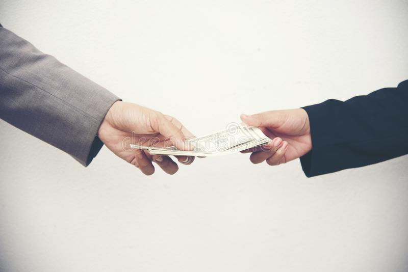 Businessman giving money to business woman. Corruption concept royalty free stock photo