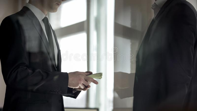 Businessman giving money to partner, profit from successful business deal. Stock photo stock photos