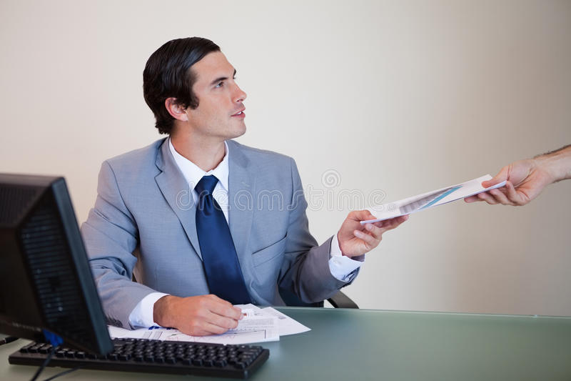 Download Businessman Giving Paperwork To Colleague Stock Photo - Image of chart, computer: 22362362