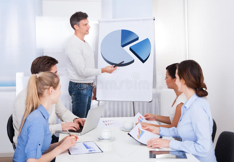 Businessman giving a presentation in meeting stock image