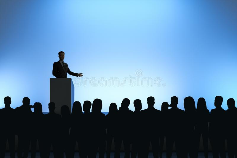 Businessman giving speech. In front of backlit audience on light blue background. Speaker and leader concept stock images