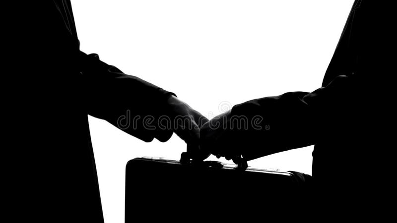 Businessman giving suitcase to partner, underground economy, illegal deal, bribe stock photography