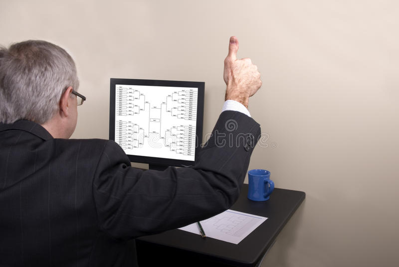 March Madness Businessman Thumbs Up. A businessman giving thumbs up looking at his March Madness barcket stock photography
