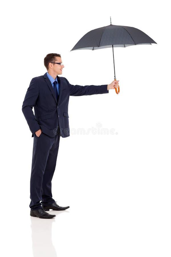 Businessman giving umbrella stock images