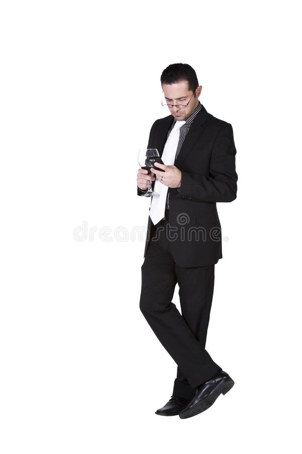 Businessman with a glass of drink texting royalty free stock photography