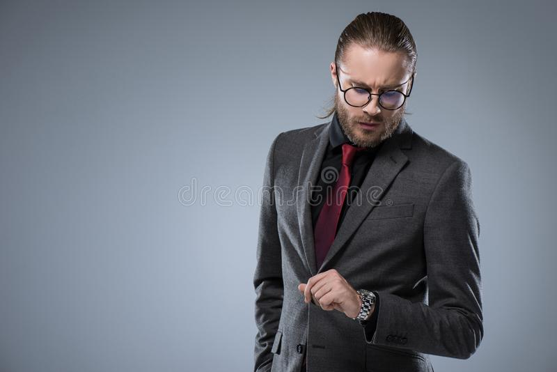 Businessman in glasses looking on his watch,. Isolated on gray stock photos