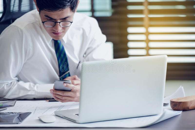 Businessman in glasses sitting at office using mobile phone royalty free stock photography