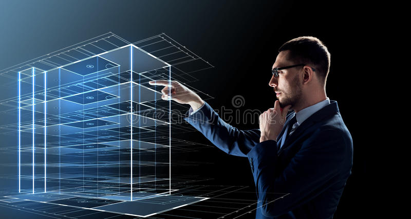 Businessman in glasses with virtual building. Business, people and future technology concept - businessman in glasses with virtual construction hologram over royalty free stock image