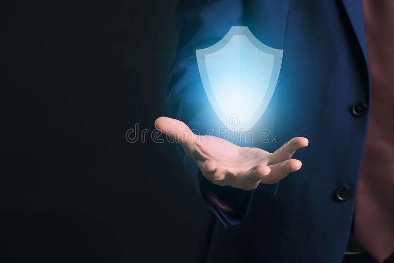 Businessman with glowing shield icon on dark background. Data security concept stock photography