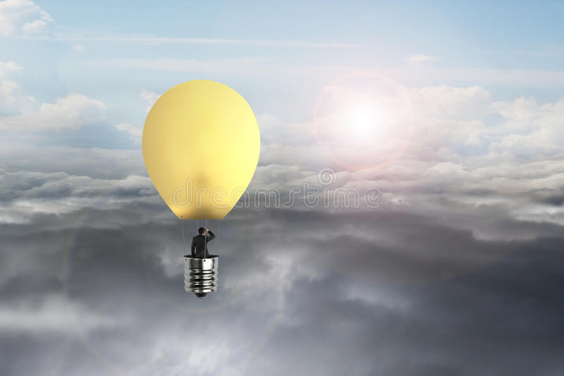 Businessman in glowing yellow lightbulb hot air balloon flying. Over natural sky daylight cloudscape background stock photos