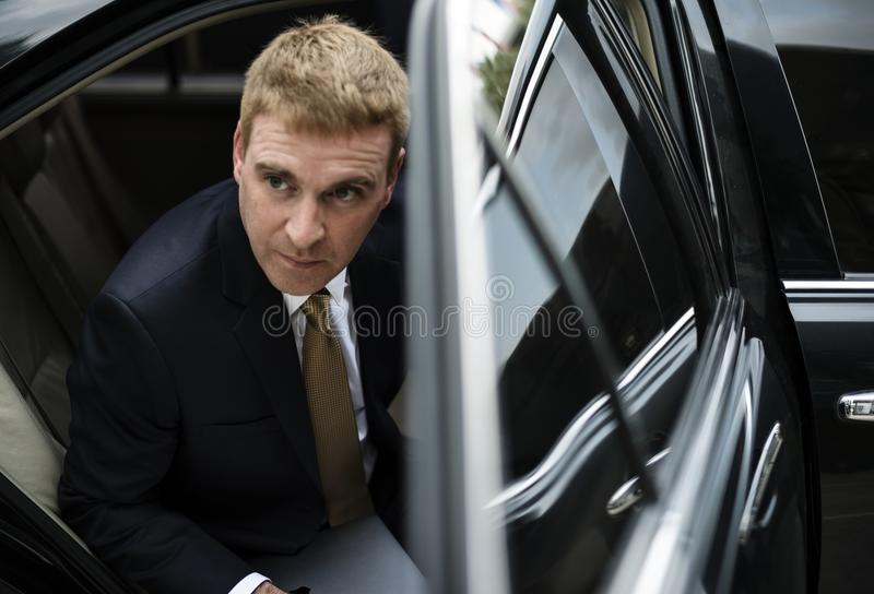 Businessman going out of his car stock photography