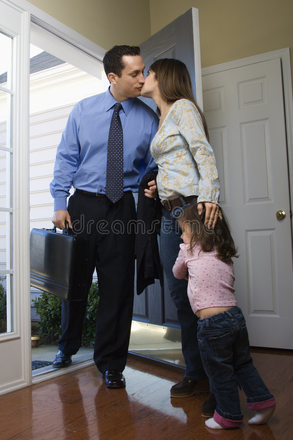Businessman going to work. Caucasian businessman at open door kissing wife while daughter hugs her leg